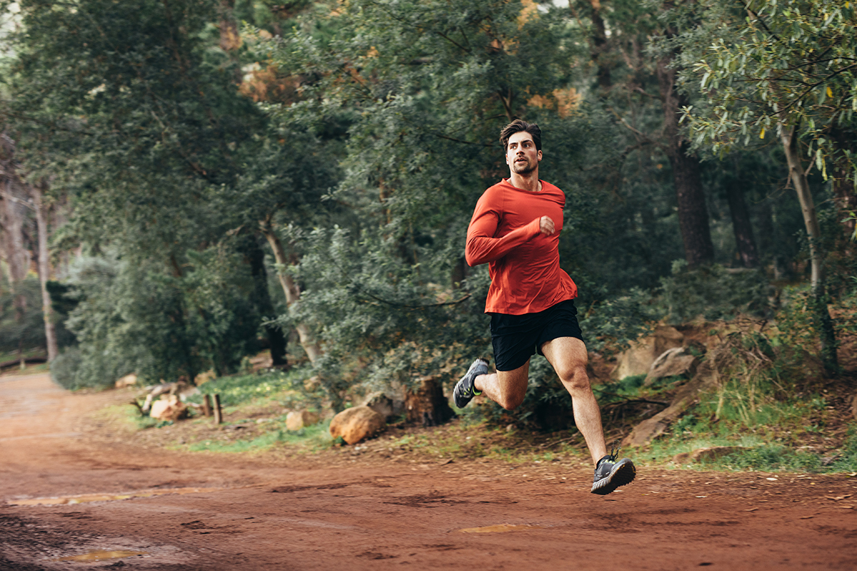 Man running on mud track. Athlete running fast in a park with dense trees in the background.